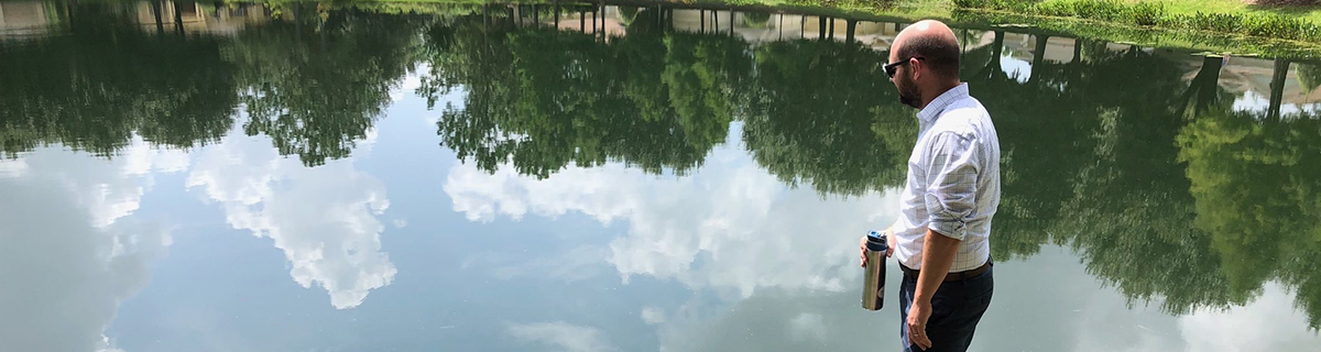 Man standing over very calm pond reflecting the sky and trees